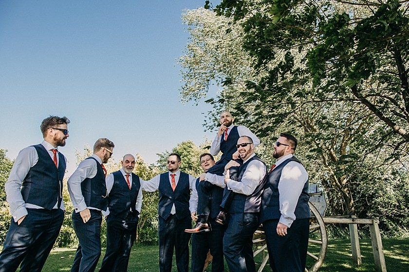 groomsmen holding groom on shoulders