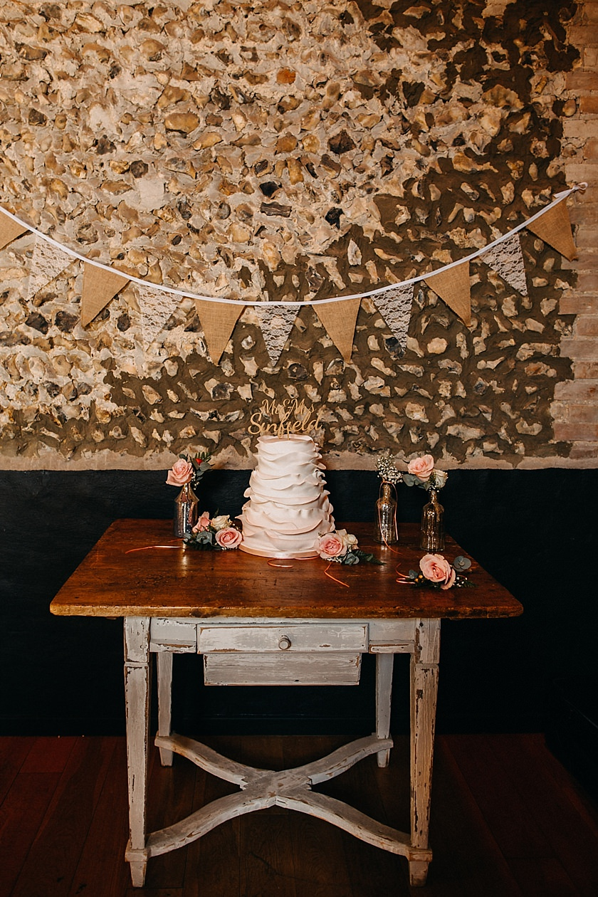 wedding cake standing on rustic white table photographed by Wedding Photography At The Granary Estates