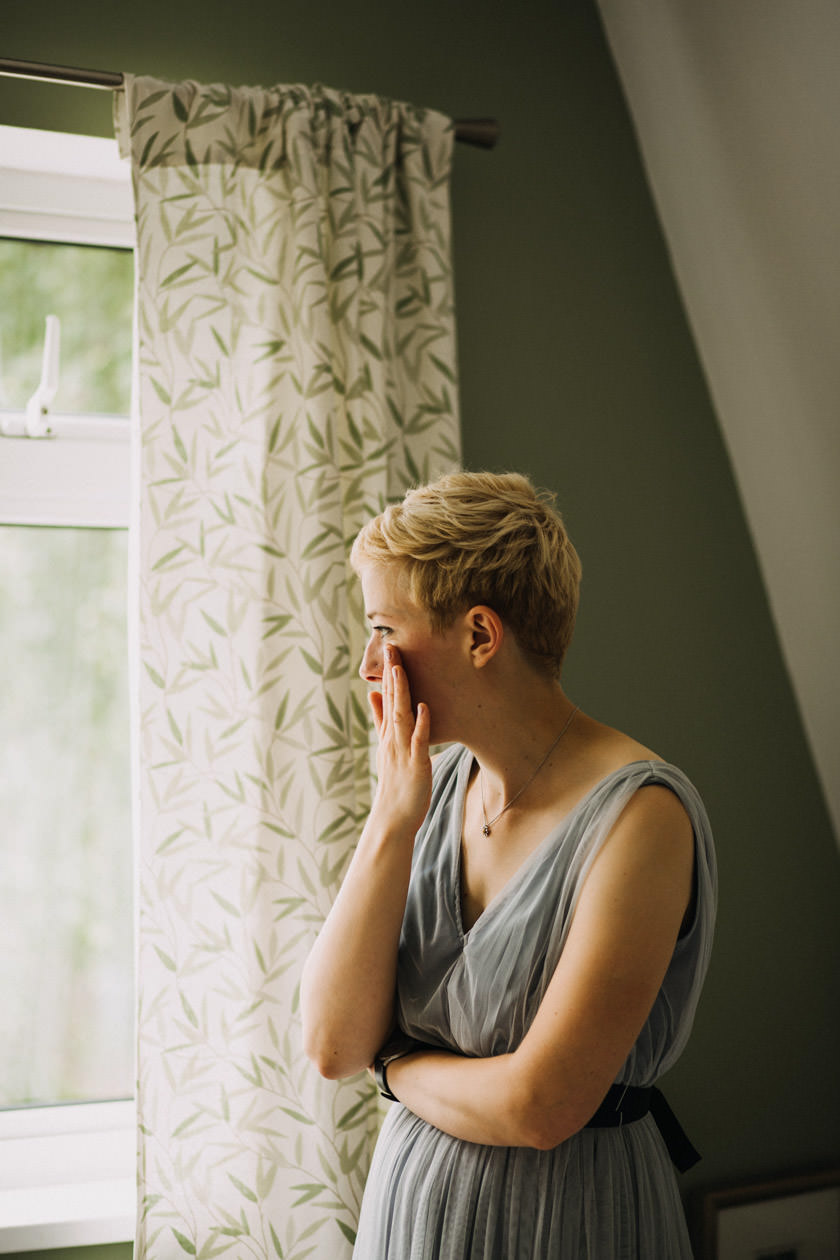 girl standing by the window wiping a tear from cheek