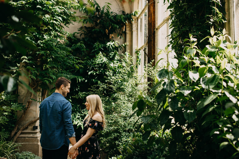 boy and girl holding hands looking at each other standing in the orangery