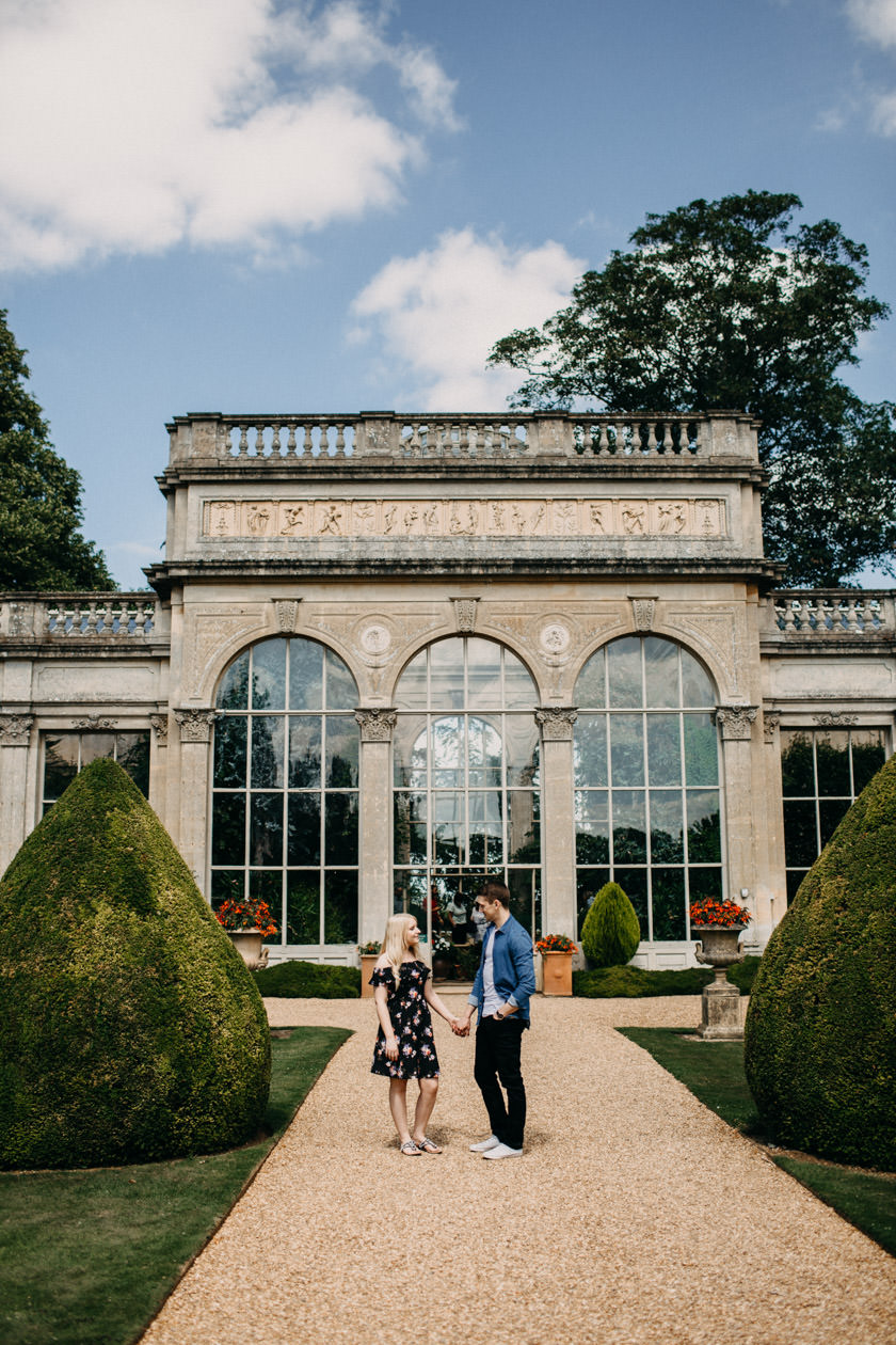 boy and girl holding hands standing in front of Castle Ashby Pre Wedding Shoot