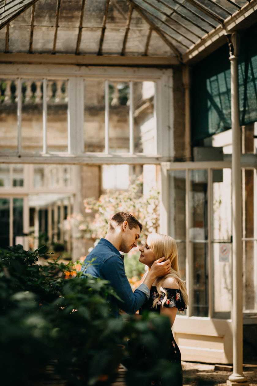 boy holding girls face and almost kissing Castle Ashby Gardens Pre Wedding Shoot