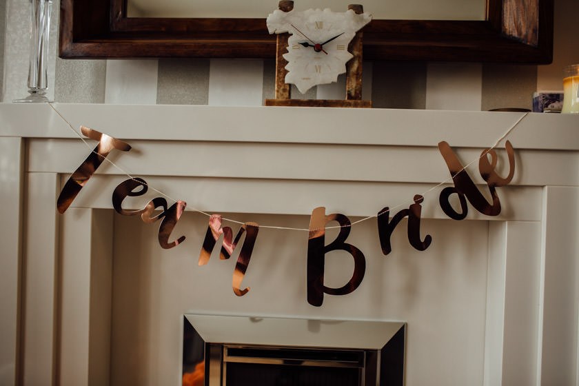 Rose Gold 'team bride' signage over a fireplace