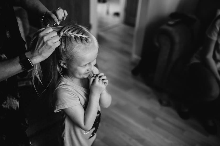 Black and white photo of little girl having her hair done. smiling and happy