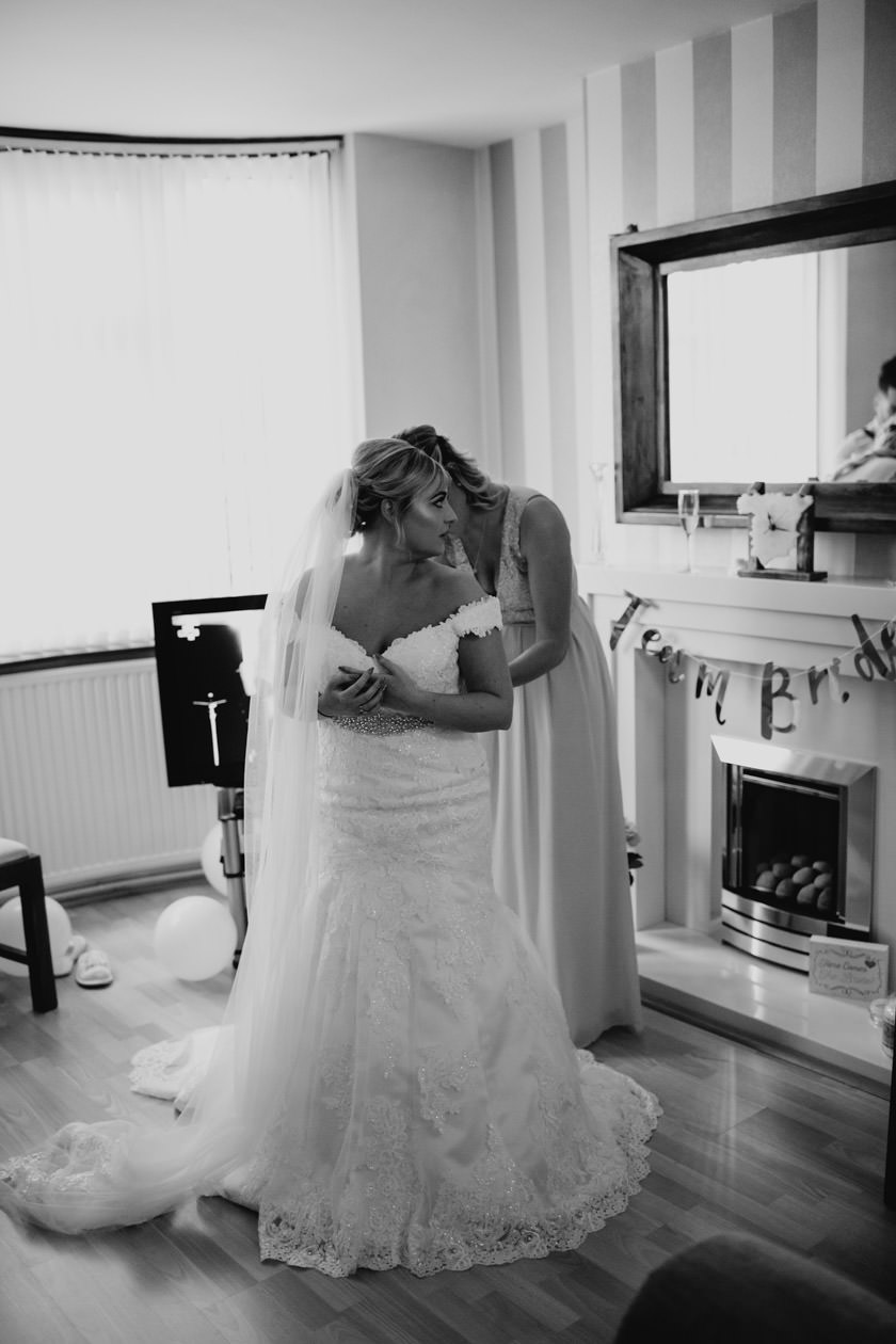 bride having her wedding dress put on by her bridesmaid. Captured by documentary wedding photographer