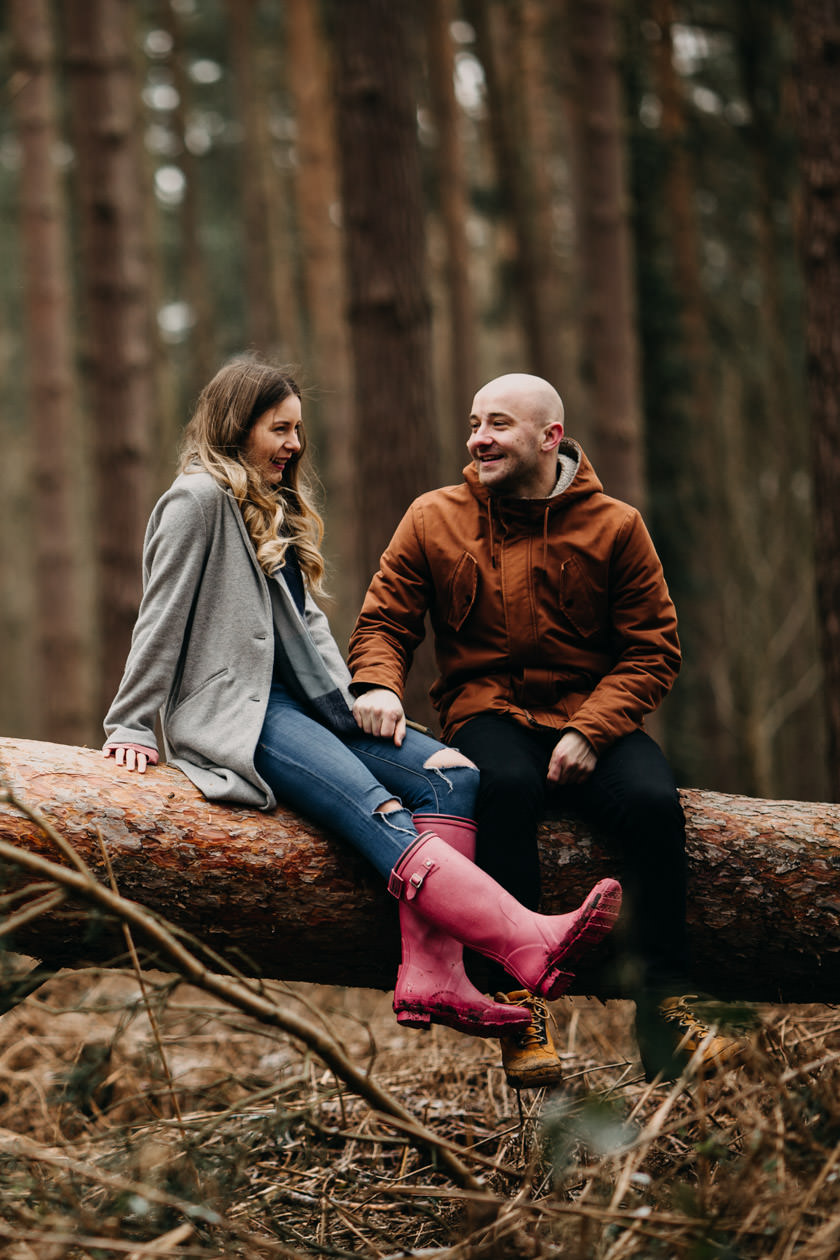 girl sitting next to a boy on a wooden log in forest smiling