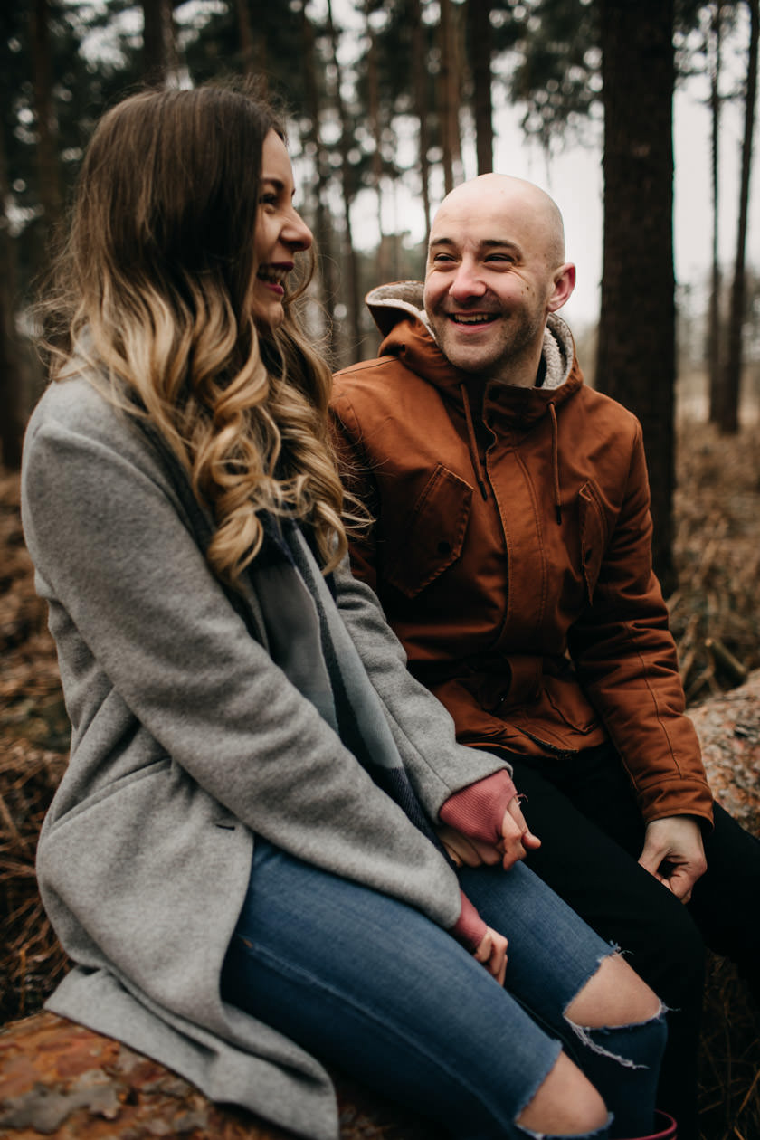 boy and girl laughing and holding hands at Pre wedding shoot at Harlestone Firs