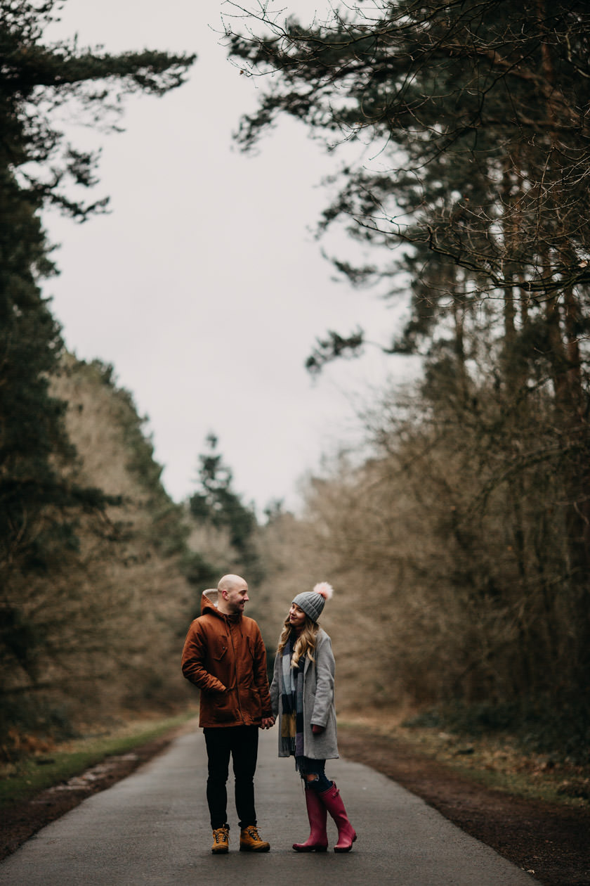couple standing on a road holding hands and looking at each other at Pre wedding shoot at Harlestone Firs, Northampton