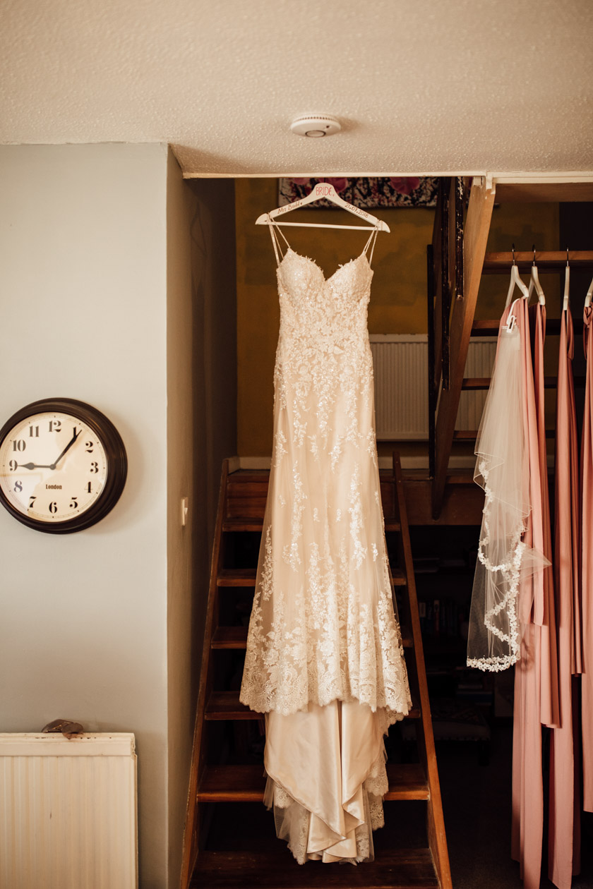 maggie sottero dress hanging on the stairs photographed by Park Farm Wedding Photographer