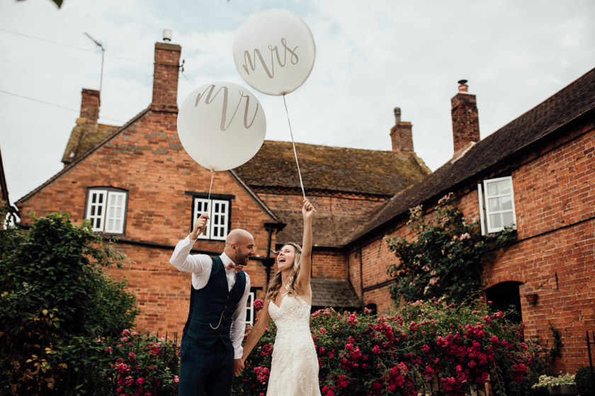 bride and groom holding huge mr & mrs balloons photographed by Park Farm Wedding Photographer