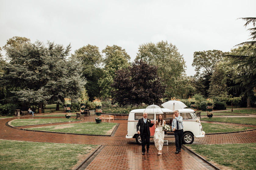 bride walking towards Nottingham Wedding Photographer with two men holding umbrellas over her head
