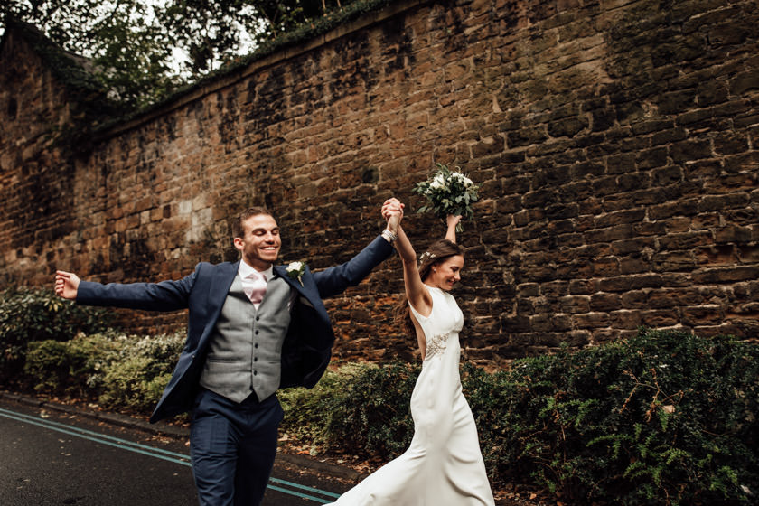 wedding couple running holding hands photographed by Nottingham Wedding Photographer