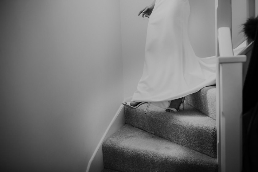 brides legs and shoes showing as she's walking down the stairs