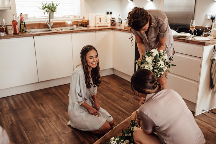 bride sitting on floor kitchen admiring flowers Nottingham Wedding Photographer