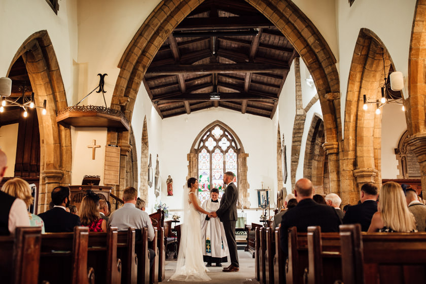 bride and groom in a church holding hands photographed by Wedding Photography Northampton