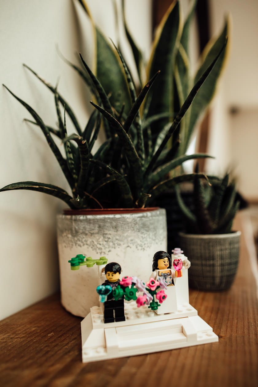 bride and groom lego figures standing by plant