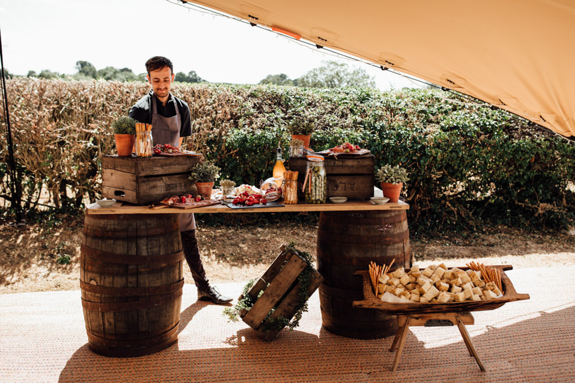 antipasti station with a selection of food and a man standing behind the stand