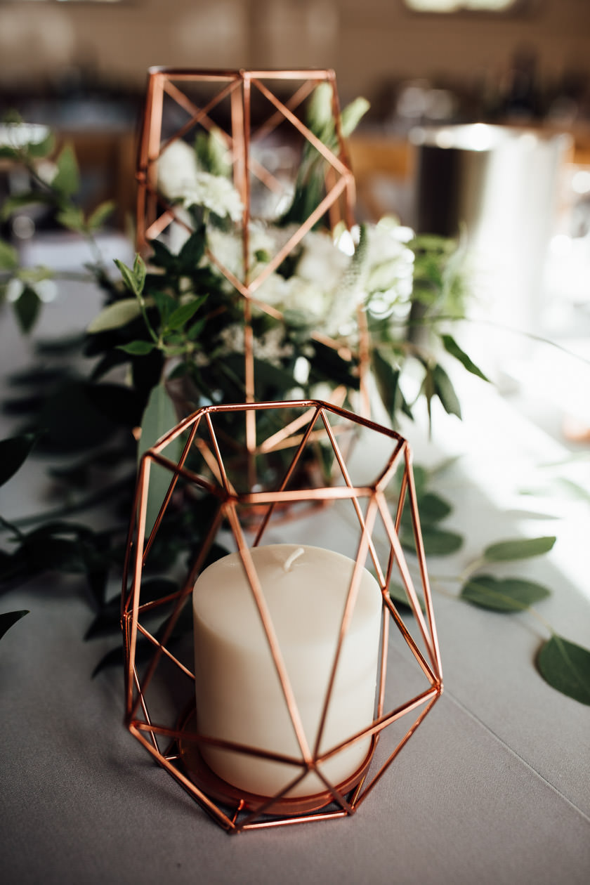 geometric copper candle holder with a white candle inside