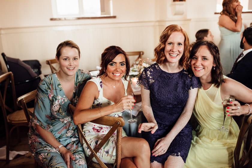 four girls sitting next to each other smiling and looking directly at the camera