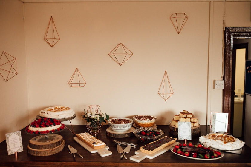 selection of cakes on a table with geometric figures pinned to a wall