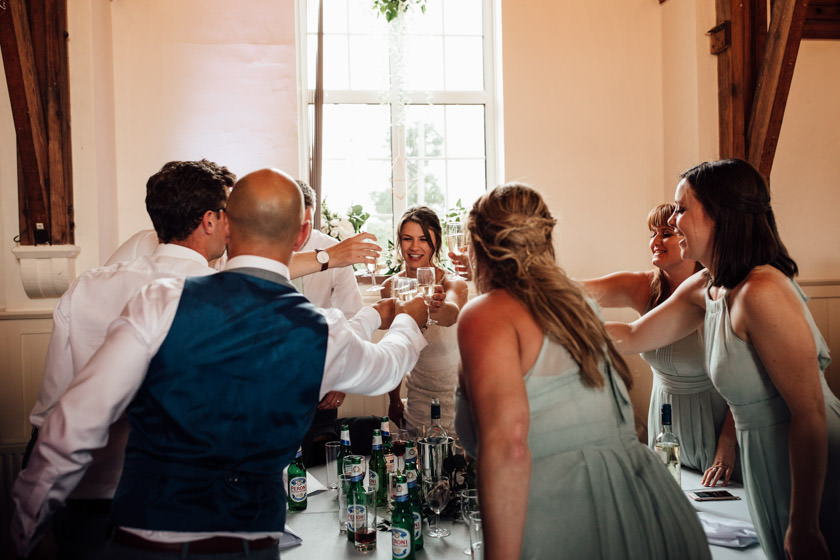 group of people by the wedding table cheering with the glasses