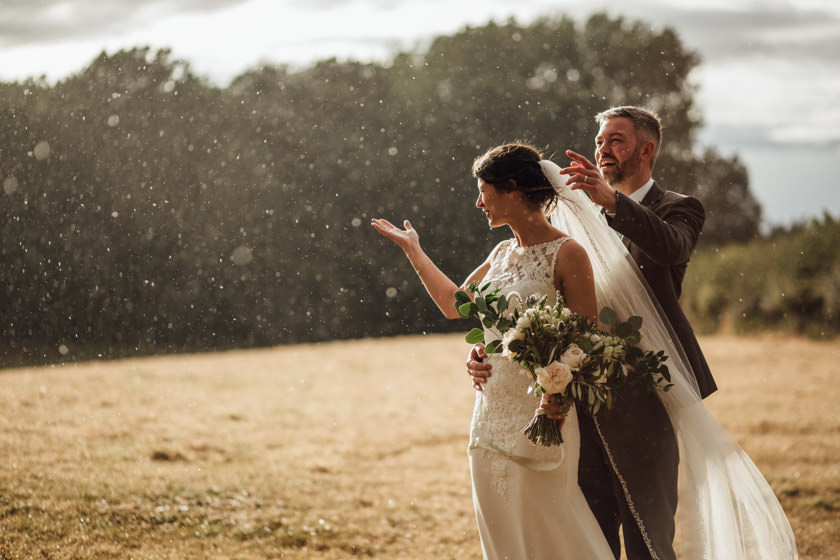 bride and groom on a field in rain