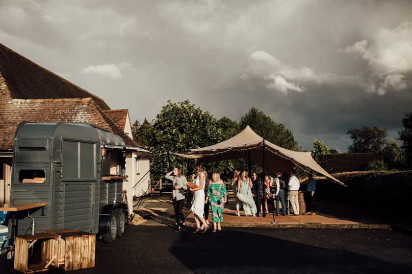 guests hiding under stretched tent getting drinks from a horse box bar
