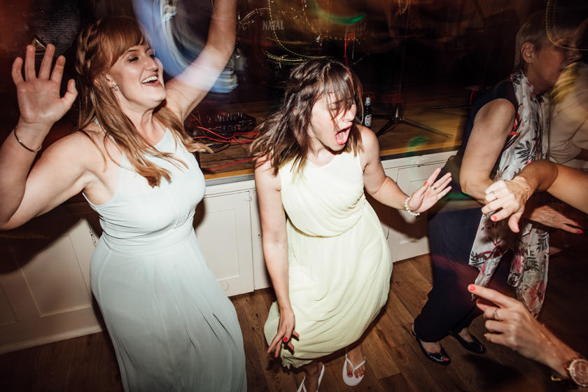 three girls dancing crazy with their hands up photographed by Wedding Photography Northampton