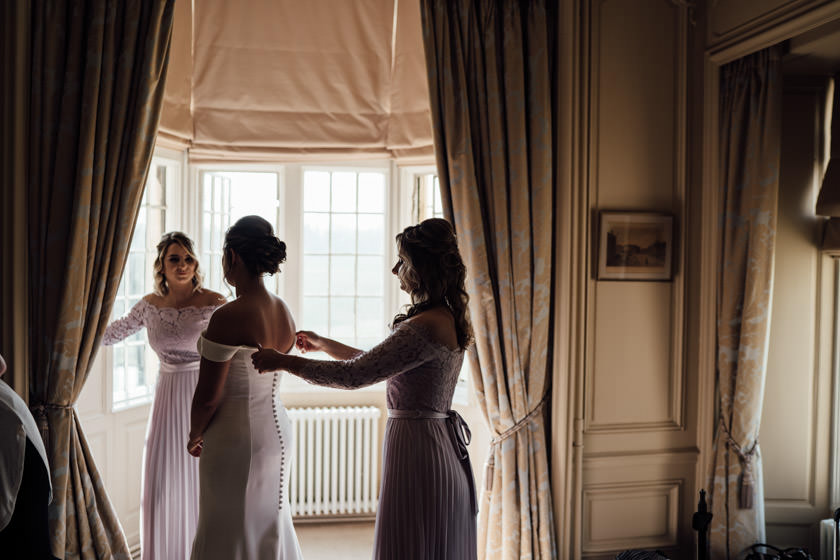 bridesmaind adjusting brides dress by the window photographed by Rushton Hall Wedding Photographer