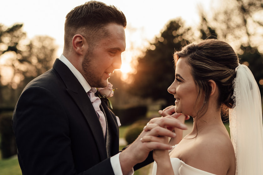 bride and groom look at eachother and holding hands photographed by Rushton Hall Wedding Photographer