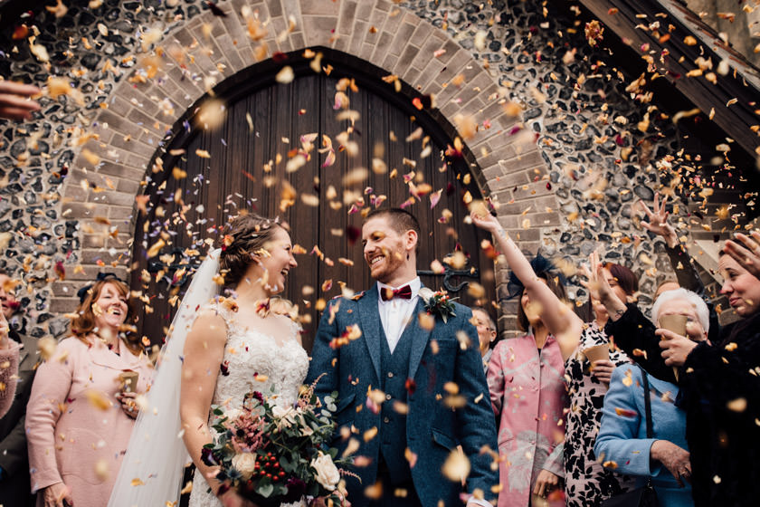dried petals confetti thrown over newly wed couple