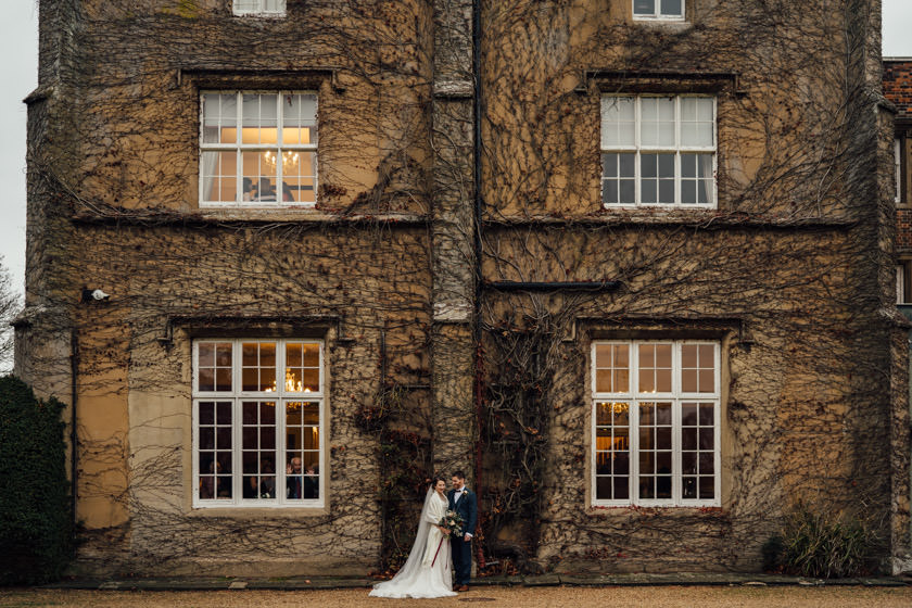 bride and groom facing eachoter standing by side of the building at offley place wedding