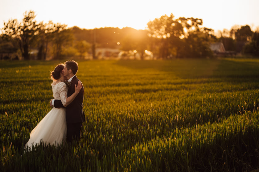 bride and groom cuddling on field during sunset