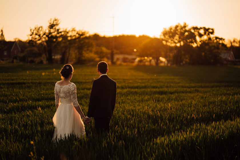 bride and groom looking at the sunset on fields The Granary Barns Wedding Photos