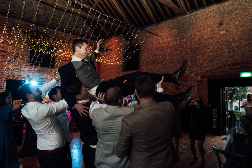 groom being lifted by a few men