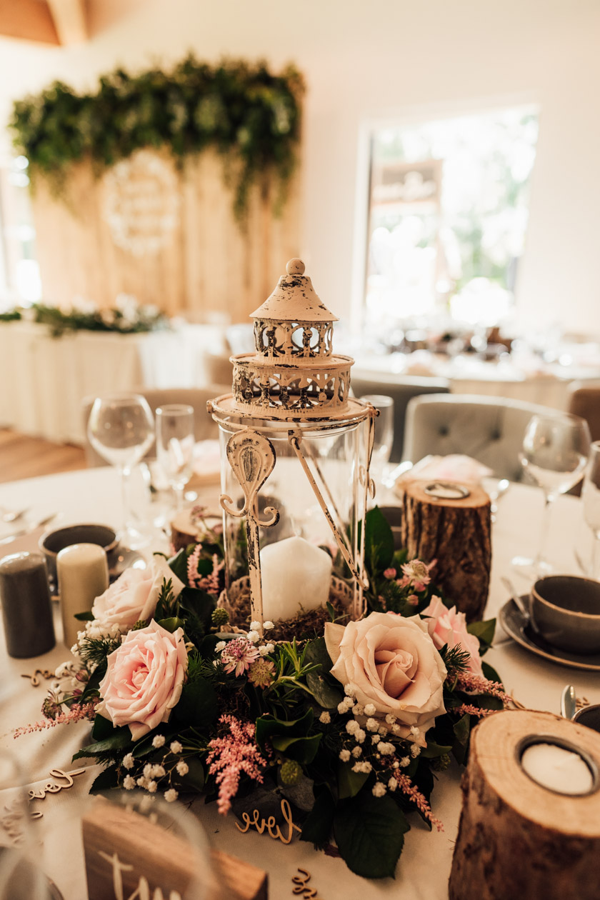 large candle holder surrounded by pink flowers as centerpiece