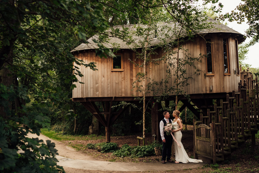 married couple standing outside a tree house