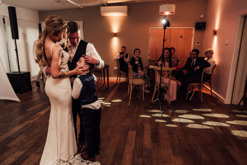 bride, groom and their son cuddling up during first dance