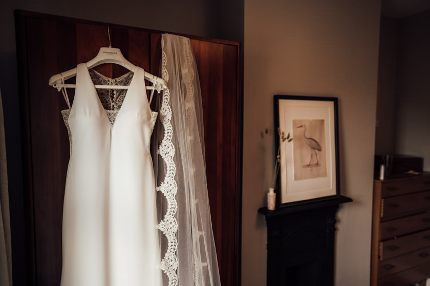 wedding dress and veil hanging on wardrobe