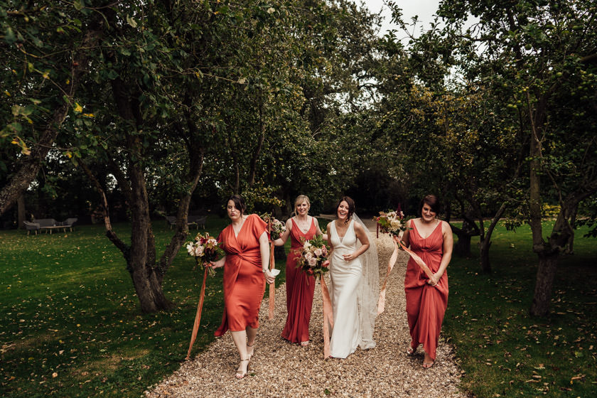 bride with her bridesmaids in orange dresses walking