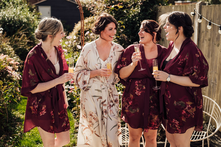 girls in robes standing outside with glass of champagne
