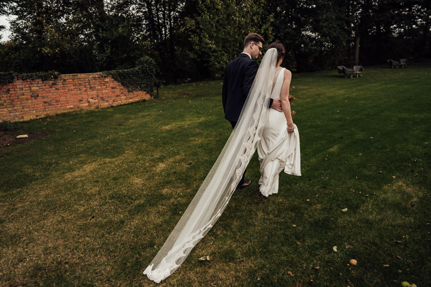 bride and groom walking back with long veil at Dodmoor House