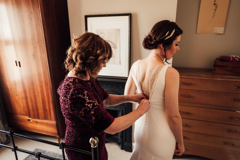 mother doing up daughters wedding dress