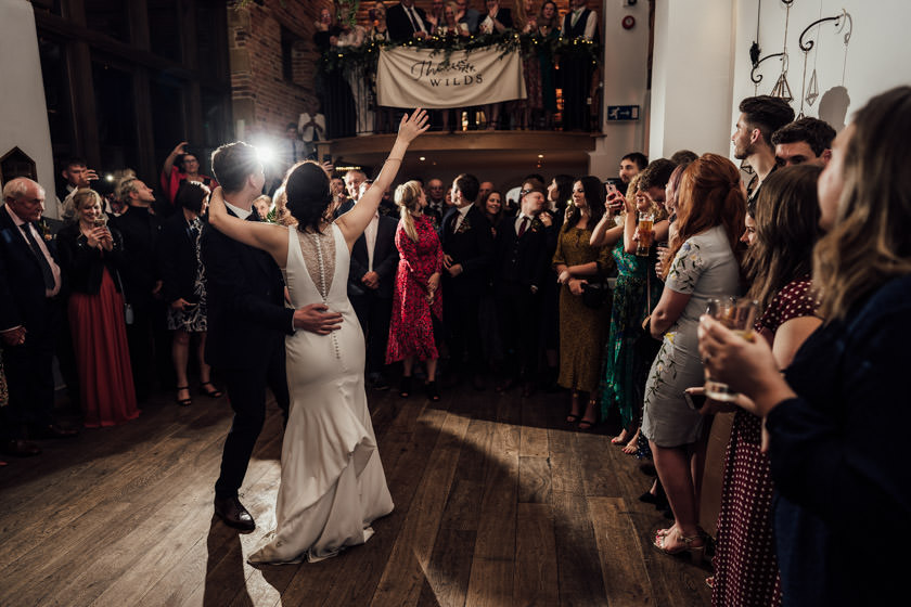 couple with hands up in air during first dance