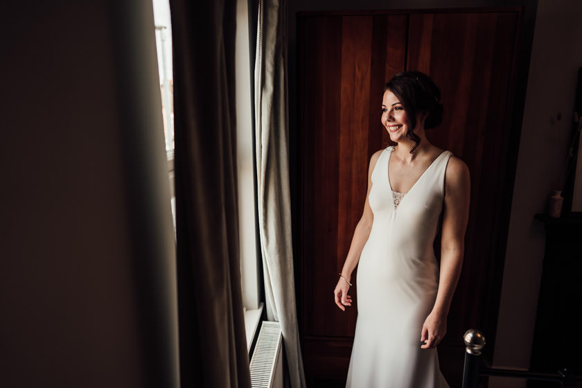 bride in white dress looking out the window