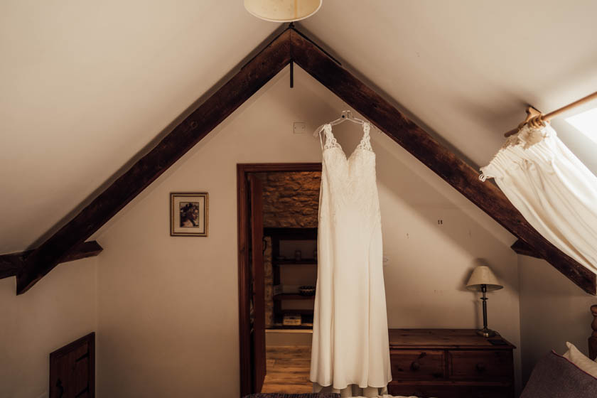 wedding dress hanging on a wooden beam